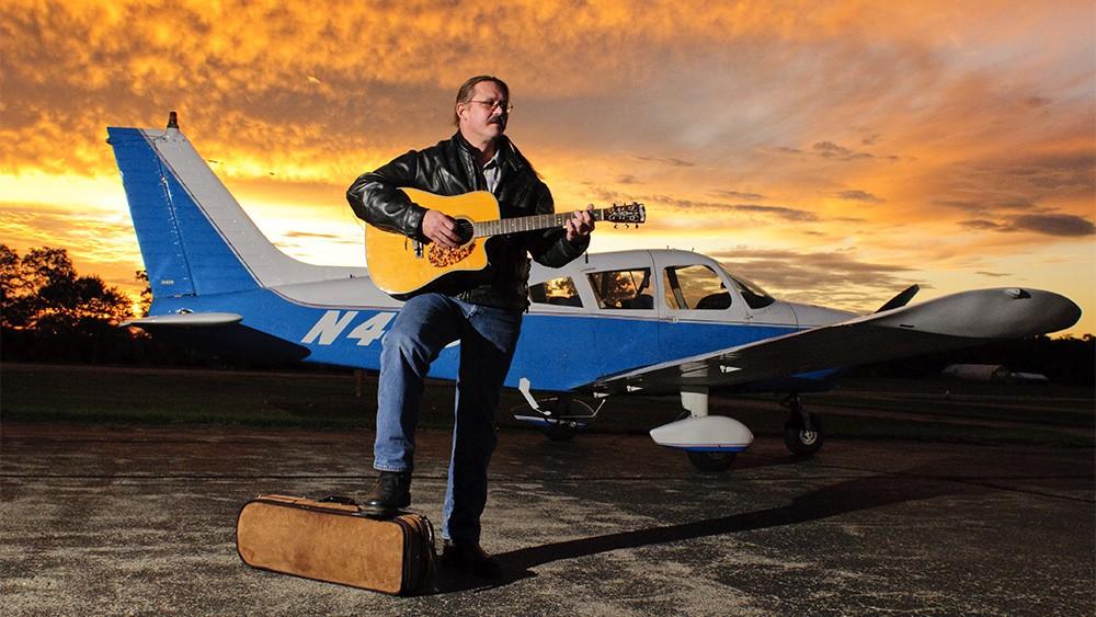 joe-martin-musician-guitar-plane-airport